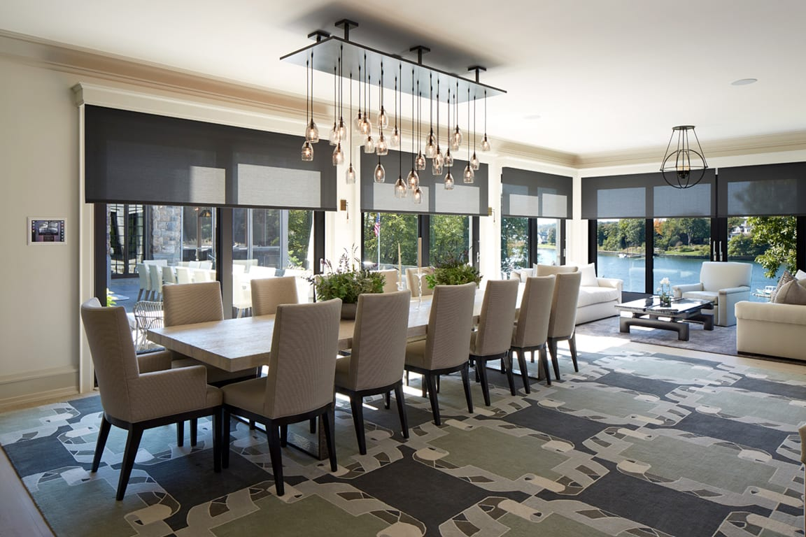 A modern dining room with a chandelier looking into minimalist kitchen